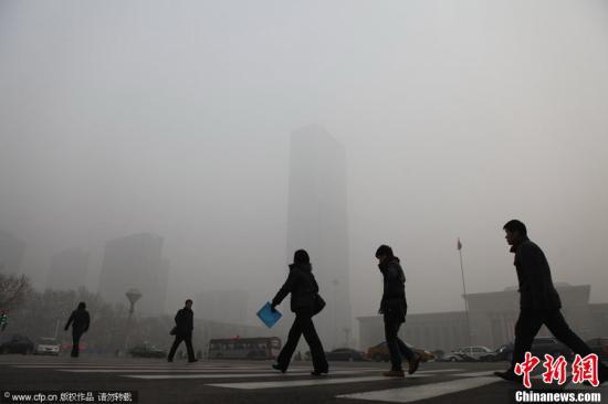 资料图:河北省石家庄被大雾笼罩,市民从石家庄最高楼开元环球中心前走过。崔靖 摄 图片来源:CFP视觉中国