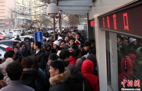 資料圖:北京朝陽區房屋登記發證大廳外排隊領號準備辦理過戶手續的市民。發 韓海丹 攝