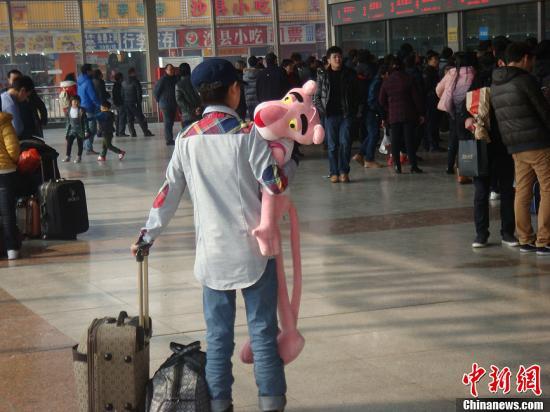 1月22日,重庆火车站迎来熙熙攘攘的人流,人们行色匆匆地踏上旅途,准备回家过年。而随着重庆高校寒假的到来,外地学子也将踏上归途,学生情侣在车站凝望、话别、拥抱,依依惜别。图为女孩抱着毛绒玩具站在火车站售票厅里。白永茂摄