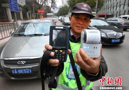 资料图:1月30日,江苏南京天津路停车收费员展示停车收费刷卡POS机。泱波 摄