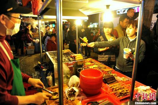 资料图:通过自由行来到台湾的两位大陆江苏女孩正在台北士林夜市品尝美食。<a target='_blank' href='http://www.chinanews.com/'>中新社</a>发 王东明 摄
