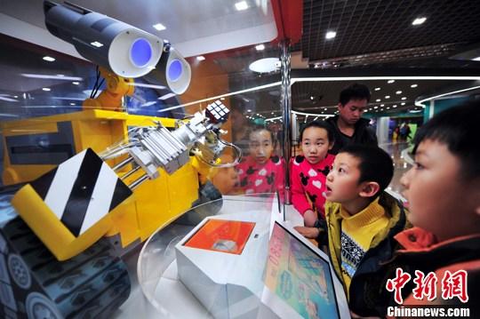 """2月22日,沈阳科学宫机器人与虚拟世界科普展开馆,现场展示了中国机器人及数字技术未来发展的全新概念演示,吸引了数百名小学生前来参观体验。图为""""解魔方机器人""""吸引小学生前来参观。中新社发 于海洋 摄"""