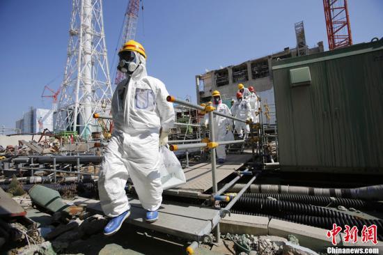 3月6日,时值福岛核事故两周年前夕,东京电力公司开放福岛第一核电站面向在日外国媒体的采访。经过抽签后,部分在日外国媒体作为代表前往福岛第一核电站进行采访。图为全副武装的东电员工带领记者前往存放核燃料棒的燃料池视察。中新社发