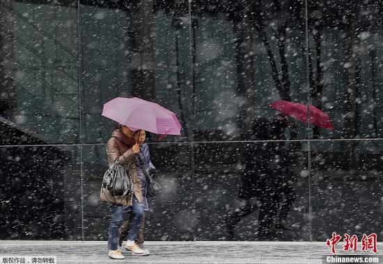 資料圖:當地時間2013年3月11日,英國多地遭遇大雪襲擊,氣溫驟降至冰點以下。圖為人們冒雪在倫敦街頭前行。