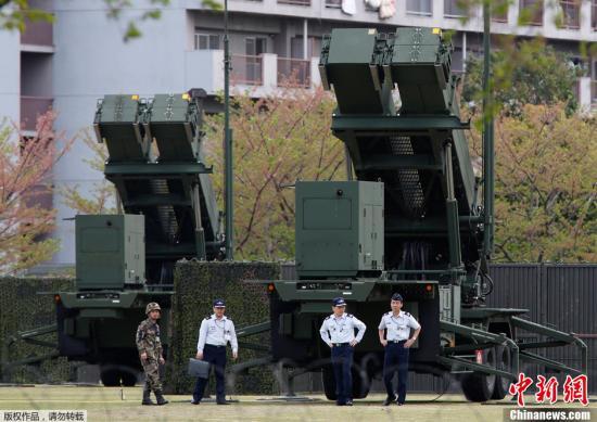 """当地时间2013年4月9日  ,日本东京  ,日本自卫队士兵在""""爱国者3""""导弹附近走动。据报道  ,日本航空自卫队将""""爱国者3""""型地对空拦截导弹PAC3部署到了东京市市谷日防卫省驻地内  ,为朝鲜发射导弹做好拦截准备。"""