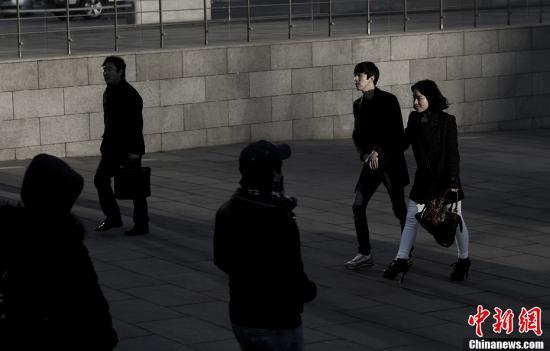 一对情侣从地下通道走进光化门广场。因为国门开放较早,韩国人具有一些西方人开放的特性,同时保留了东方人的含蓄。他们也许会在大街上牵手而行,却不会有美国式的奔放。<a target='_blank' href='http://www.chinanews.com/'>中新社</a>发 刘关关 摄