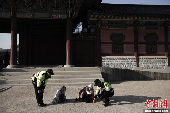 资料图:韩国两位警察与两位小女孩一起玩耍。 /p中新社发 刘关关 摄