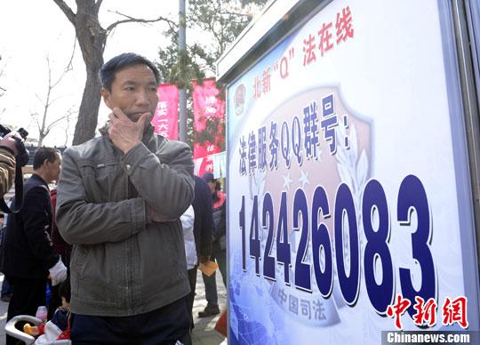 资料图:市民留意公布法律服务QQ群号的展板。<a target='_blank' href='http://www-chinanews-com.dmdby.com.cn/'>中新社</a>发 侯宇 摄