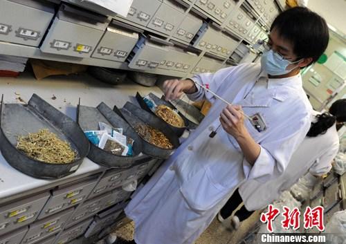 4月13日,一名中药师在福建省第二人民医院中药房现场操作如何用藿香、金银花、大青叶、芦根中药材配制成预防人感染H7N9禽流感的中药。中新社发 刘可耕 摄