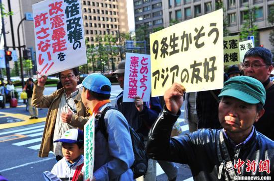 """5月3日是日本""""宪法留念日""""。因为安倍晋三下台后屡次公布示意其修宪欲望,使得这个留念日成为""""护宪派""""高密度亮相的一天。3500名日本大众当日下午汇集在东京市内的日比谷公园,举行否决修宪会议及反对游行。图为游行步队中高举爱护""""宪法9条""""、呐喊亚洲敌对的大众。中新社发 孙冉 摄"""