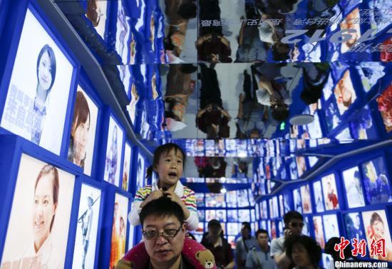 """5月19日,游客在北京园博会台湾园""""溯源 一路走来""""照片长廊中穿行。照片谱写了台湾人口的构成以及迁徙历史,其中,大部分照片的主人公是在大陆工作的台湾人,或者是在台湾工作的大陆人,或者是与两岸关系有密切关系的人,两岸同胞血浓于水的亲情不言而喻。中新社发 刘关关 摄"""