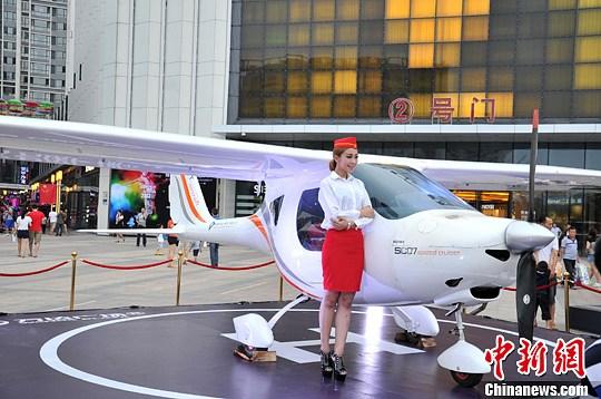 """资料图:一辆私人飞机与一名""""空姐""""亮相福州某商场门口。<a target='_blank' href='http://www.chinanews.com/'>中新社</a>发 吕明 摄"""