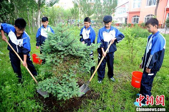 """6月17日,黑河市爱辉区幸福乡中学开展了以""""爱树节水""""为主题的植树活动。中新社发 邱齐龙 摄"""