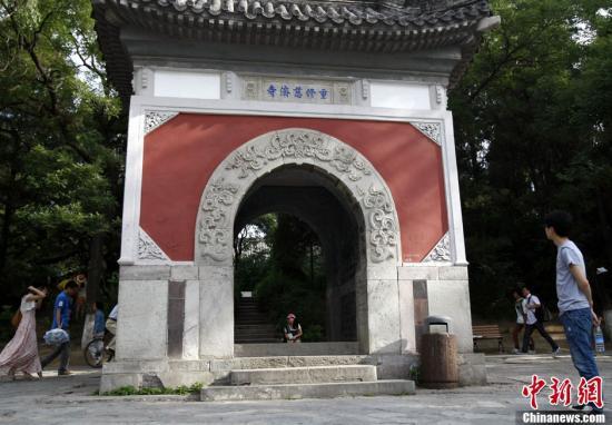 6月18日,游客正在北京大学未名湖畔的慈济寺山门遗址附近参观。发 李慧思 摄