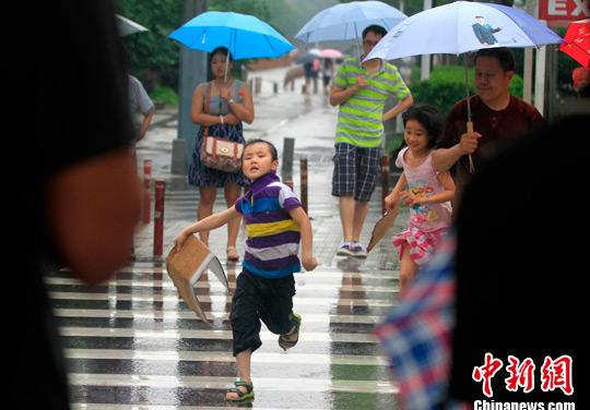 �D�橐幻�小男孩奔跑在大雨中。(�Y料�D)中新社�l ���� �z