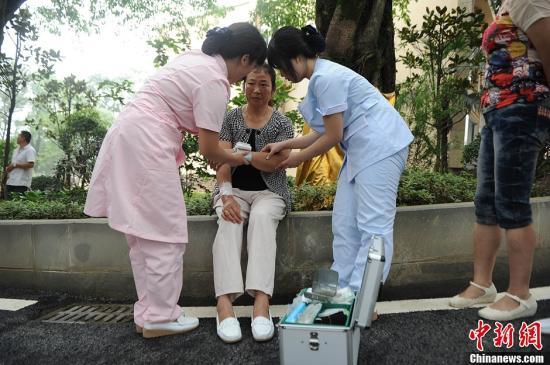 资料图:养老院内,医务人员在进行包扎工作。陈超 摄