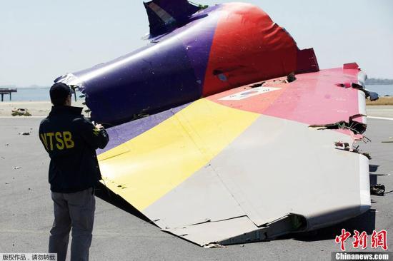 当地时间7月7日,美国国家运输安全委员会(NTSB)调查员在坠机现场调查韩亚航空214航班的尾段。