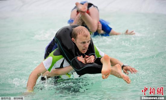 """资料图:当地时间2013年7月6日,芬兰松卡哈维举行世界""""背老婆""""锦标赛。现场妙趣横生。背老婆大赛最早出现在芬兰的松卡哈维,要求男子携女性队友在最短时间内完成一段障碍赛。"""