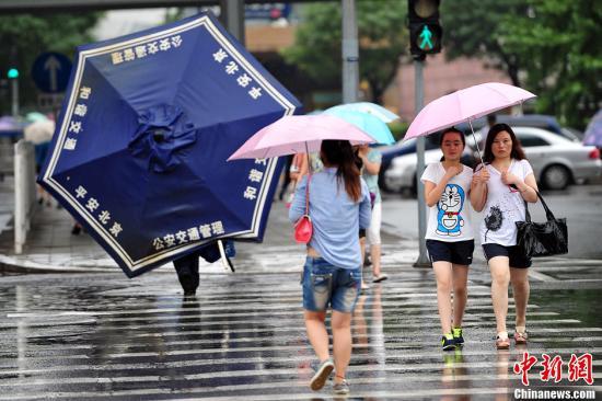 资料图:民众在暴雨中行走。中新网记者 金硕 摄