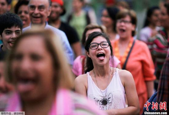 """资料图:委内瑞拉加拉加斯,民众在广场上参加""""笑声疗法""""集会。委内瑞拉""""笑声疗法""""专家称笑声可以缓解人们的紧张情绪平复心情,增强人们的幸福感。"""