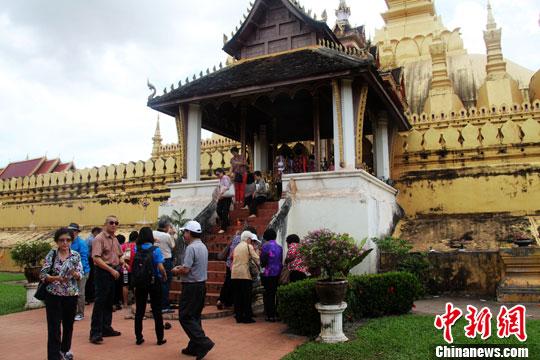 8月2日,老挝首都万象著名景点塔銮寺内,一群泰国游客在轮流上香。中新社发 张明 摄