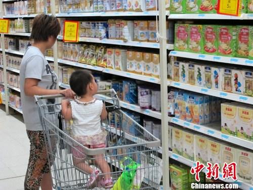 8月4日,北京一大型超市内,一名市民带孩子挑选婴幼儿奶粉。新西兰乳制品巨头恒天然集团2日向新西兰政府通报称,其生产的3个批次浓缩乳清蛋白(WPC80)中检出肉毒杆菌,影响包括3个中国企业在内的8家客户。<a target='_blank' href='http://www.chinanews.com/'>中新社</a>发 崔楠 摄