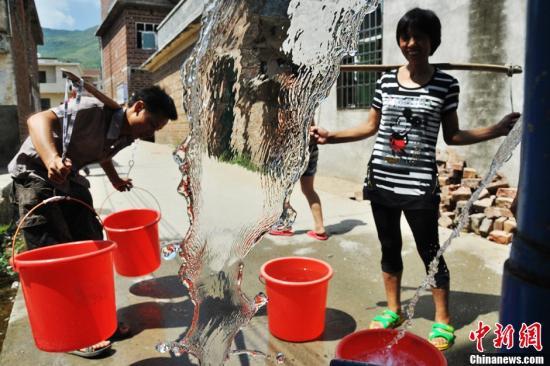 8月5日,工作人员在给桂阳县流峰镇麻布村送来饮用水,解决了1200余村民的生活用水问题。为保证人畜用水安全,该县每天派专人到各个生活用水困难区送水四次,确保村民生活用水正常。从6月12日起,湖南省桂阳县持续高温少雨,累计降雨量18.1毫米(县城关站),比历年同期均值偏少232.2毫米,创历史记录同期最低,全县26个乡镇(街道)全部受灾,3.09万余人存在饮水困难,25.38万亩农作物受旱,3.59万亩晚稻无水下插。罗泽勤 摄