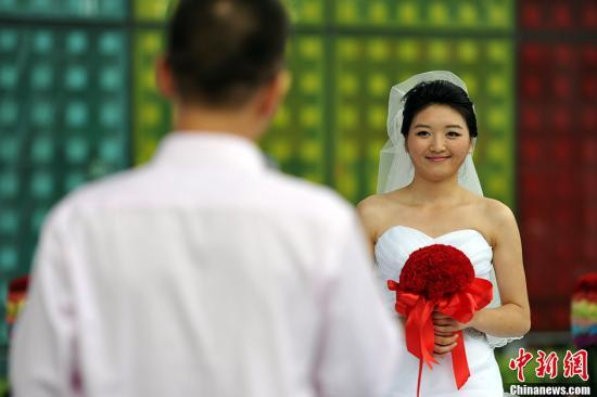 资料图为婚礼上新郎向新娘表达爱意。记者 金硕 摄