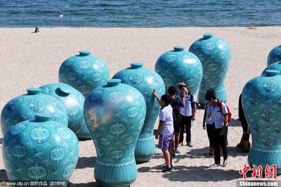 """资料图片:韩国釜山,海滩上举办""""大海美术节"""",游客们正在欣赏作品。图片来源:CFP视觉中国"""