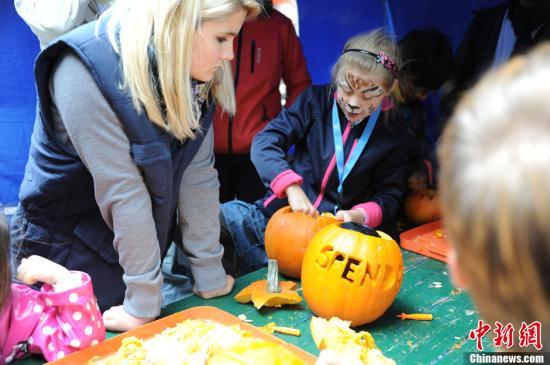 """当地时间9月22日,由联合国儿童基金会以及德国""""儿童救援协会""""主办的""""世界儿童日""""在柏林波茨坦广场举行。该活动一年举行一次,本届的主题为""""给儿童机会""""。组织者为不同年龄段的孩子提供适合的玩乐节目。图为大人带领孩子做南瓜灯。<a target='_blank' href='http://www.chinanews.com/'>中新社</a>发 黄霜红 摄"""