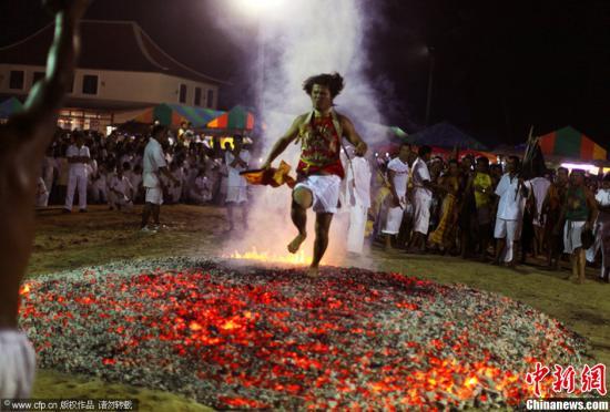 """当地时间2013年10月10日,泰国普吉岛,素?#36784;?#26399;间泰国信徒表演""""下火海?#20445;?#20809;脚在烧红的炭木上跑过。图片来源:CFP视觉中国"""