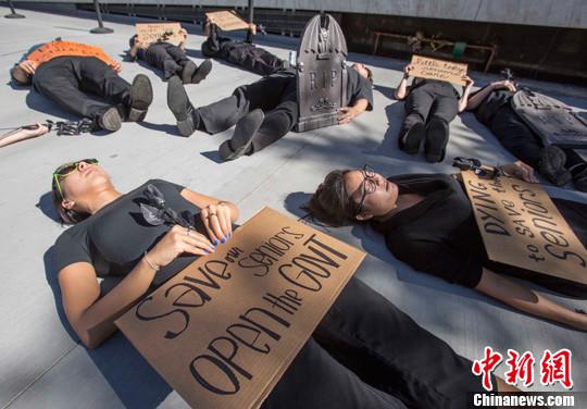 当地时间10月16日,示威者手持黑玫瑰躺在联邦大楼外抗议。当日,一群代表加州退休美国人联盟的成员在美国洛杉矶市中心联邦大楼外抗议示威,反对联邦政府关门及可能影响退休人士的社会保险福利。<a target='_blank' href='http://www-chinanews-com.hfjlzj.com/'>中新社</a>发 林戈 摄