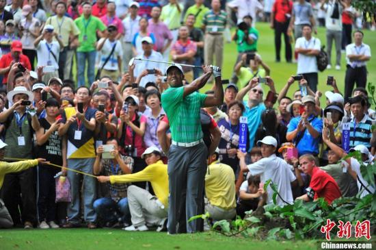 """资料图:""""老虎""""泰格・伍兹在众多球迷的关注下挥杆。<a target='_blank' href='http://www.chinanews.com/'>中新社</a>发 骆云飞 摄"""