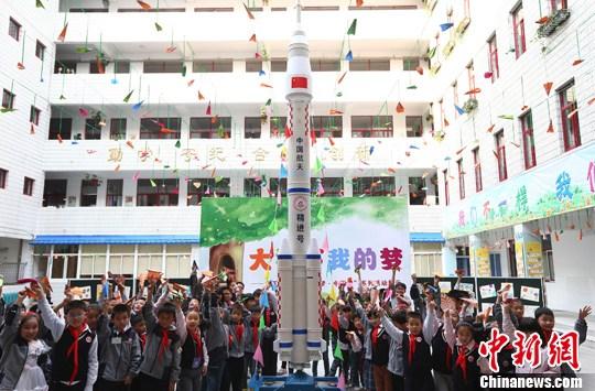 """10月29日,南京火瓦巷小学的孩子们在该校师生们用环保材料亲手制作的火箭模型前欢呼。当日,南京举办小学生""""大树下我的梦""""主题活动,集中进行小学生综合素质教育才艺展示,同时现场放飞纸飞机,预示着孩子们的梦想会飞的更高更远。发 泱波 摄"""