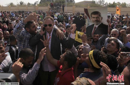 资料图:2013年11月4日,在穆尔西受审的开罗警察学院外,其支持者高喊口号参加示威。