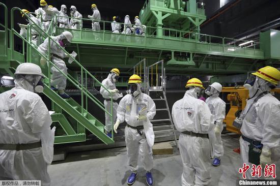 资料图:日本东京电力公司的员工和媒体记者们身着防护服,进入福岛第一核电站4号反应楼调查。