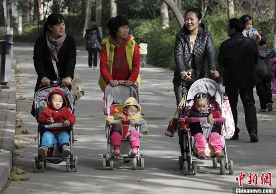 资料图:2013年11月15日,河南郑州几位家长推着婴儿车走过郑州街头。中共十八届三中全会审议通过了《中共中央关于全面深化改革若干重大问题的决定》,《决定》提出,启动实施一方是独生子女的夫妇可生育两个孩子的政策。中新社发 王中举 摄