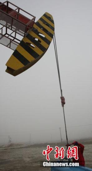 11月20日,一名采油女工冒着大雾正在克拉玛依油田八区油区巡井。周建玲 摄
