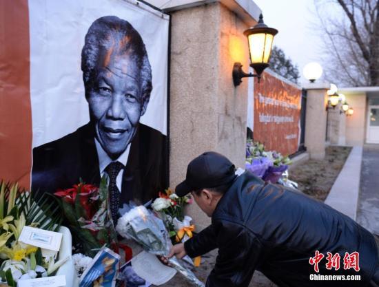 资料图:一名中国民众在位于北京的南非共和国驻华使馆外,向曼德拉的大幅画像敬献鲜花,对曼德拉的逝世表示哀悼。<a target='_blank' href='http://www.chinanews.com/'>中新社</a>发 侯宇 摄