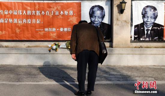 资料图:2013年12月6日 ,一名中国男子来到北京南非驻华大使馆前,向曼德拉画像鞠躬。<a target='_blank' href='http://www.chinanews.com/'>中新社</a>发 张浩 摄