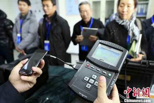 资料图:北京市检察院工作人员向来访民众展示介绍UFED手机检验工具。发 李慧思 摄