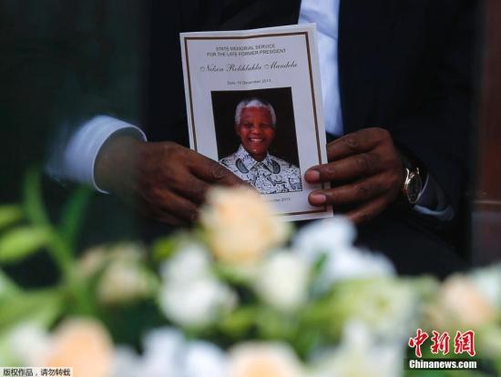 资料图:民众手举曼德拉肖像。