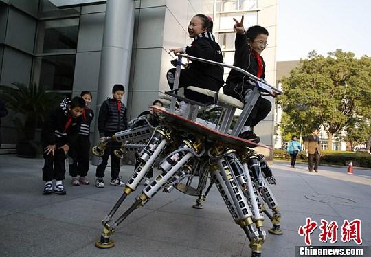 """12月10日,在上海科技馆举行的科普讲堂上,一群儿童与一台机器人来了个""""亲密接触"""",近距离感受机器人的魅力。中新社发 汤彦俊 摄"""