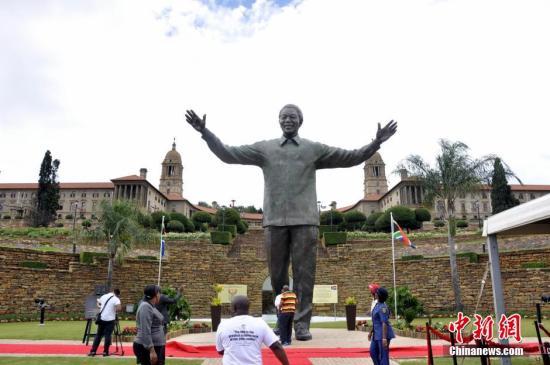 """12月16日,一座高9米的新曼德拉雕像在南非行政首都比勒陀利��正式揭幕,上�f民�在��y府前聚集��C�v史性的一刻。新曼德拉雕像是一座高9米��~雕像,于12月13日用吊��⑿侣�德拉雕像放置在��y府供人民瞻仰。南非每年的12月16日是法定假日""""和解日"""",南非政府�⑿碌裣窳料嗳掌诙ㄓ凇昂徒馊铡毕笳髦�在南非�v史上一��新�r代的�_始。�D�樾碌裣裨陉�光照射下熠熠生�x,曼德拉面�Т认榈奈⑿Γ����_�p臂如同�肀д�座城市。中新社�l �⒗� �z"""