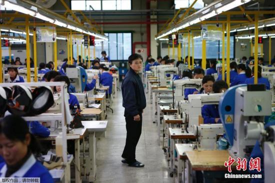 当地时间12月19日,开城工业园区,朝鲜工人在工厂工作。