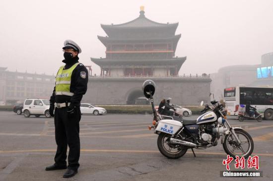 资料图:一位交警戴着口罩于西安钟楼前执勤。。中新社发 张远 摄