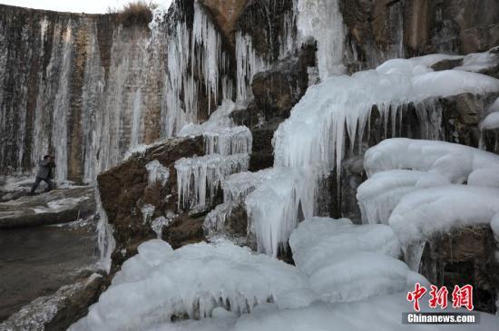 12月27日,一名摄影爱好者在山东省枣庄市山亭区北庄镇一处塘坝前拍摄冰瀑景观。 受较强冷空气影响,当日山东枣庄气温骤降至-9℃,山亭区多处塘坝前出现冰瀑美景,吸引许多游人和摄影爱好者前往观赏拍照。 <a target='_blank' href='http://www.chinanews.com/'>中新社</a>发 李宗宪 摄 图片来源:CNSPHOTO