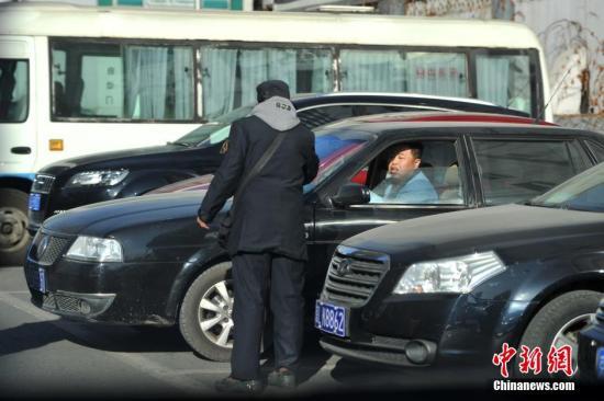 资料图:北京一停车场管理员为车主指挥倒车。<a target='_blank' href='http://www.chinanews.com/' >中新网</a>记者 金硕 摄