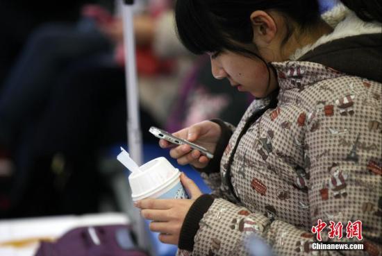 """1月23日上午,铁路青岛站候车室内,玩手机的""""低头族""""随处可见。刷微博、聊微信、玩游戏、看电影,高科技将大多旅客变为手机""""低头族""""。/p中新社发 徐崇德 摄"""