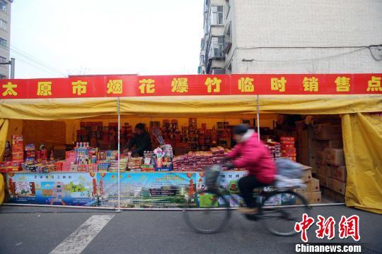 资料图:民众从烟花爆竹销售点经过。张云 摄
